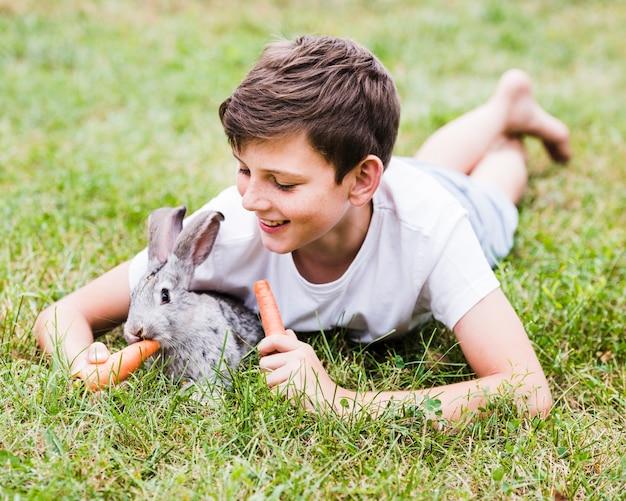 Smiling boy lying on green grass feeding carrot to rabbit