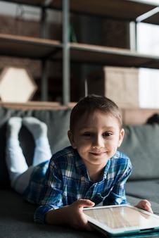 Улыбающийся мальчик на диване с планшетом
