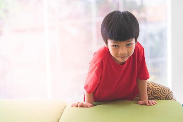 遊び場でプレイハウスの上に微笑む少年