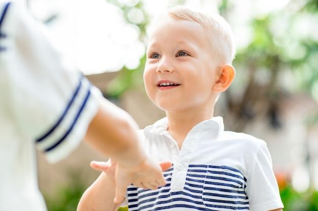 Улыбающийся мальчик, играющий с сестрой на открытом воздухе
