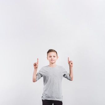 Smiling boy pointing his finger upward looking to camera isolated on grey background