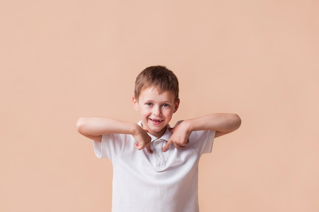 Smiling boy pointing index finger at himself standing near beige wall