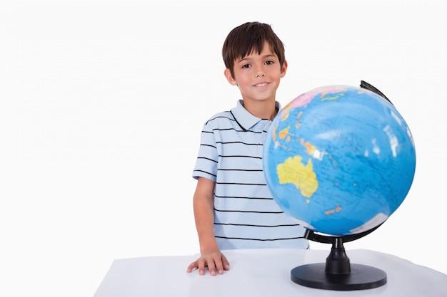 Улыбающийся мальчик позирует с глобусом