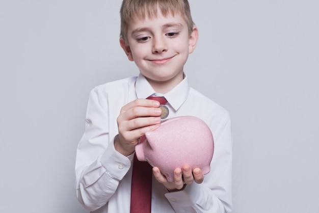 Улыбающийся мальчик кладет монету в розовую копилку