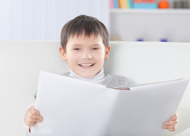 Smiling boy reading a book in the nursery