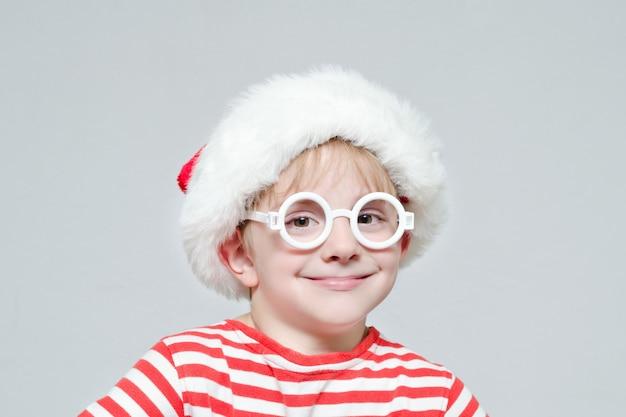 Smiling boy in santa's hat and glasses. portrait