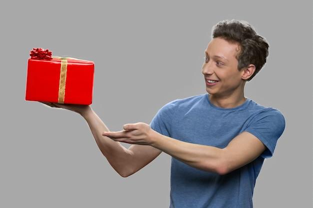 그의 손에 선물 상자를 보여주는 웃는 소년. 회색 배경에 선물 상자를 들고 십 대 남자입니다. 휴일 판매 개념.