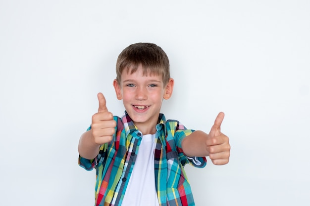 Smiling boy showing thumb up gesture on white