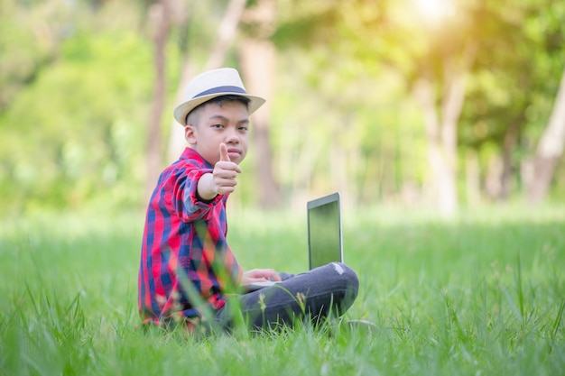 Smiling boy sitting on the grass and studying