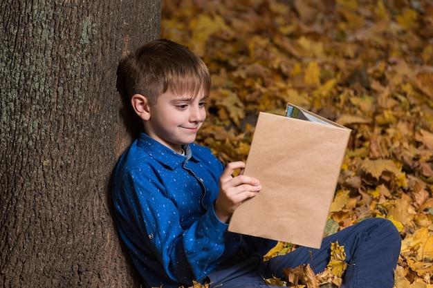 Улыбающийся мальчик сидит возле дерева в осеннем лесу и читает книгу. копировать пространство. макет.