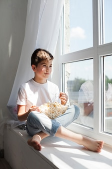 Smiling boy sitting on window sill holding bowl of popcorn and looking outside