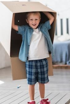 彼の頭の上に段ボール箱で立っている笑顔の少年