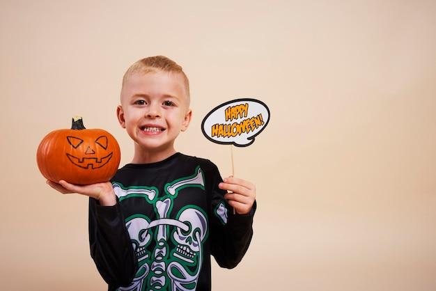 Il ragazzo sorridente inizia a decorare le zucche