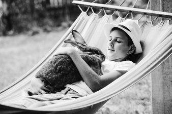 Smiling boy wearing hat lying on hammock with rabbit