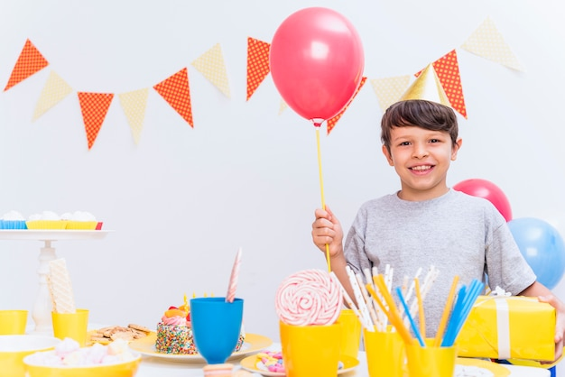 Smiling boy wearing party hat holding balloon and gift standing behind variety of food on table