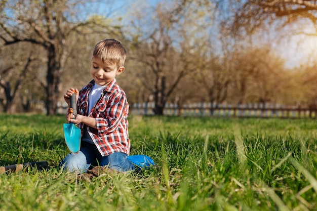 A smiling boy wearing a plaid shirt sitting on his knees and playing in a garden with a stainless soil scoop