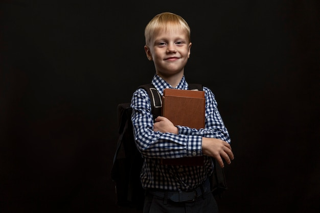 Smiling boy with a backpack and books in his hands. child 6-7 years old in a blue plaid shirt. back to school. study and education. black background.