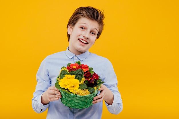 Улыбающийся мальчик с корзиной цветов в руке, в синей рубашке, изолированной на желтой стене