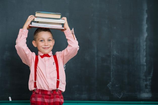 Улыбающийся мальчик с книгами на доске