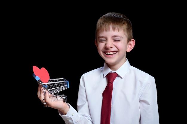 Улыбающийся мальчик с закрытыми глазами держит металлическую тележку для покупок с открыткой в форме сердца внутри. изолировать на черной поверхности.