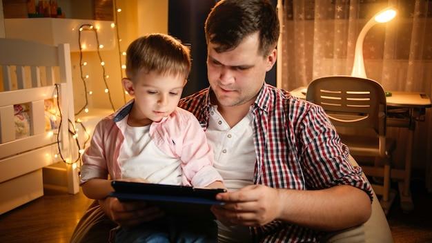 크리스마스를 위해 장식된 침실에서 태블릿 컴퓨터를 사용하는 아버지와 함께 웃고 있는 소년. 아동 교육과 가족이 밤에 함께 시간을 보내는 개념.