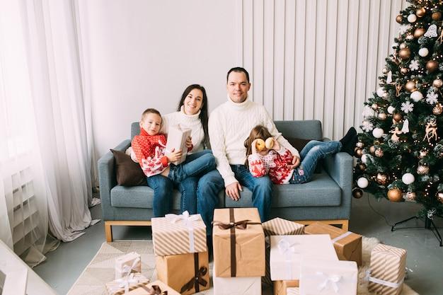 Улыбающийся мальчик с подарочной коробкой и девочка с пончиками отдыхают рядом с родителями