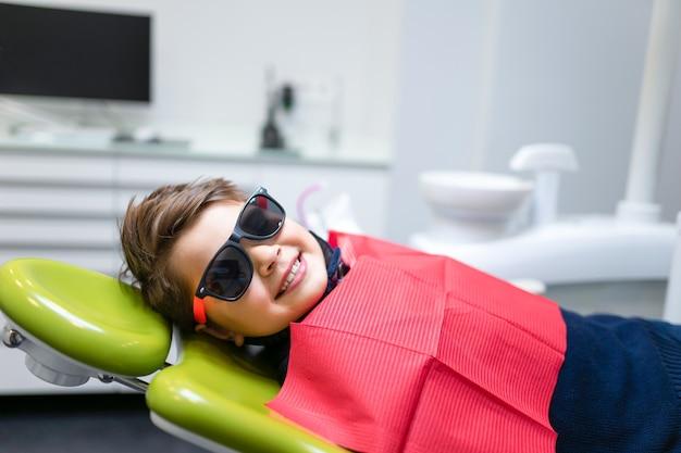Улыбающийся мальчик в очках лежит на стоматологическом кресле