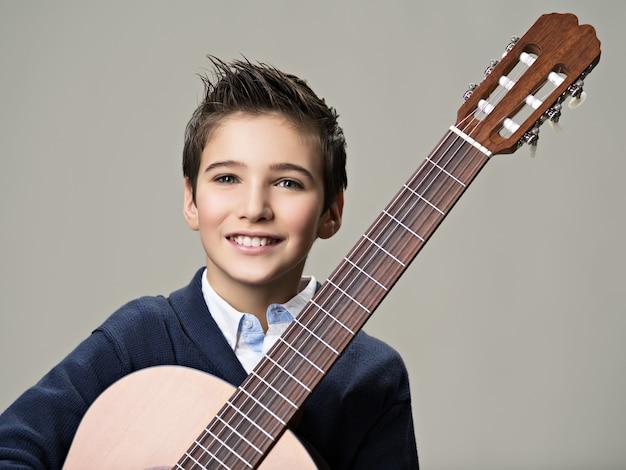 Улыбающийся мальчик с гитарой.