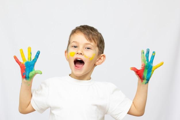 白い背景の上のペンキで手を笑顔の少年
