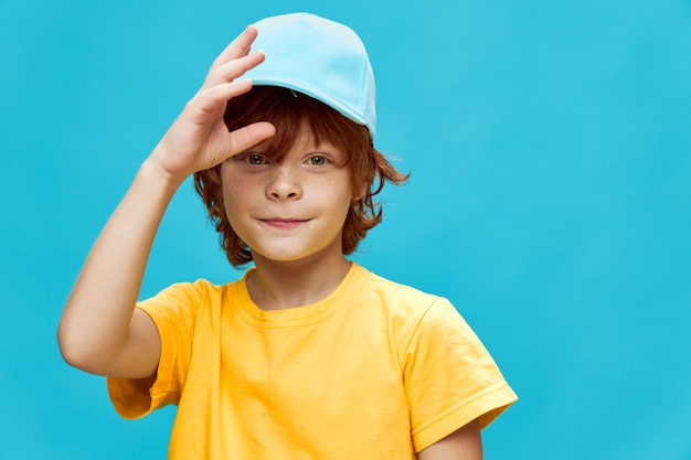 Smiling boy with red hair holds his hand near his face blue cap yellow t-shirt blue background