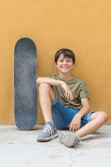 A smiling boy with skateboard sitting alone