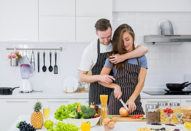 Smiling boyfriend hug woman from behind watching her preparing fruit salad in the kitchen, loving man embrace girlfriend cutting fresh fruit, romantic couple spend time at home together