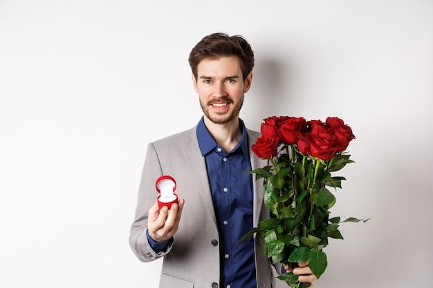 Улыбающийся парень делает предложение руки и сердца, стоя с обручальным кольцом и букетом красных роз, собирается на романтическое свидание в день святого валентина, белый фон.