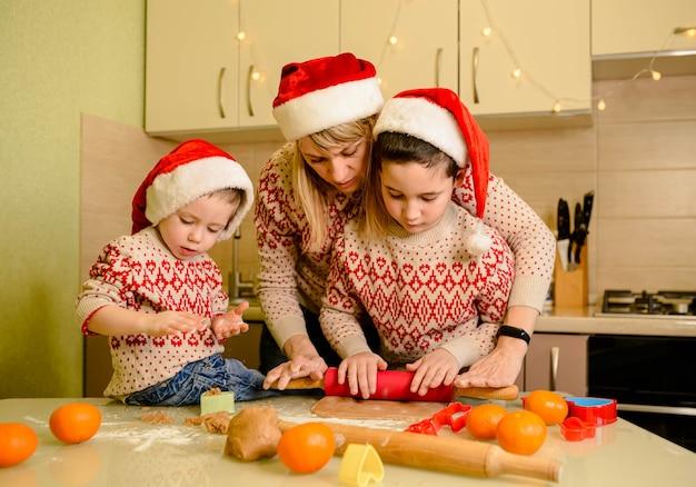 웃고 있는 소년들과 어머니는 집에서 크리스마스 쿠키를 굽고 있다