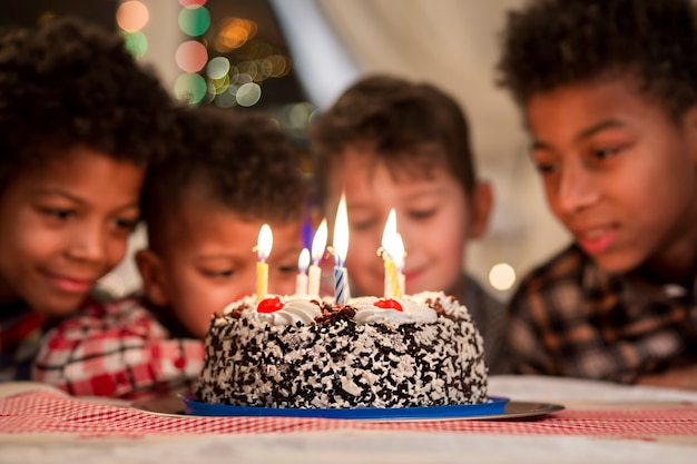 バースデーケーキの近くにいる男の子の笑顔窓の横にある男の子のバースデーケーキは、ろうそくが燃え尽きるまで待っています...
