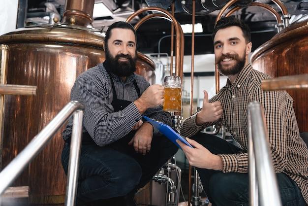 Smiling brewers drink ale in beer plant shopfloor