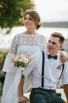 Smiling bride brunette young woman with the boho style bouquet with groom
