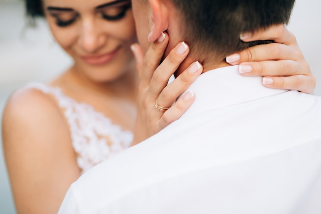 Smiling bride embraces the groom kissing her temple closeup
