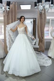 Smiling bride fitting dress in wedding salon