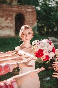 Улыбающаяся невеста передает свадебный букет своим друзьям.