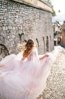 아름 다운 긴 분홍색 드레스를 입고 웃는 신부