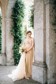 花の花束とドレスを着た笑顔の花嫁は、古代の別荘の湖のアーチの近くに立っています