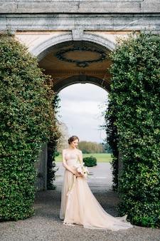 ピンクの花の花束が立っているオフショルダーのドレスを着た笑顔の花嫁