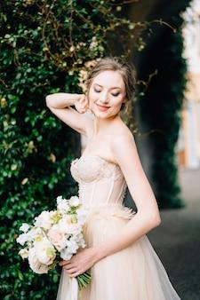 ピンクの花の花束とオフショルダーのドレスで笑顔の花嫁は彼女の頭の後ろに彼女の手を置きます