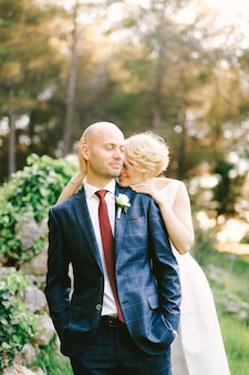 Smiling bride in a white dress hugs from behind groom in a blue checkered suit while standing in the