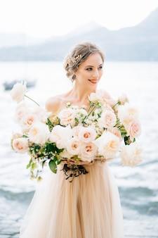 Улыбающаяся невеста с букетом цветов стоит на берегу