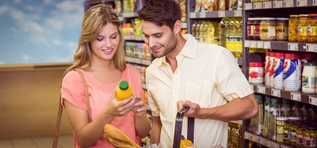 Smiling bright couple buying food products with shopping basket