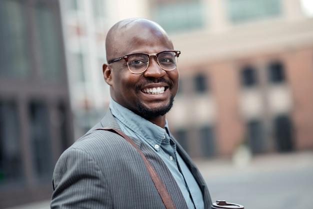 広く笑っている。やる気を感じながら広く笑っているひげを生やした浅黒い肌のビジネスマン
