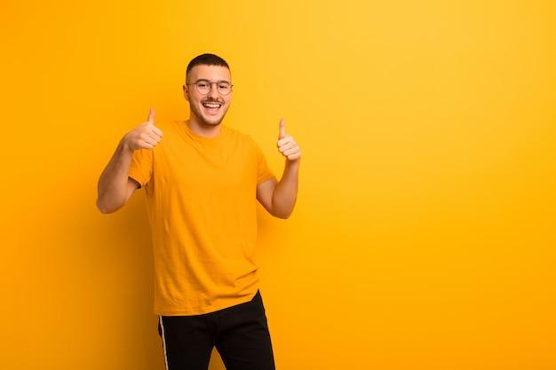 Широко улыбаясь, выглядит счастливым, позитивным, уверенным и успешным, подняв оба больших пальца