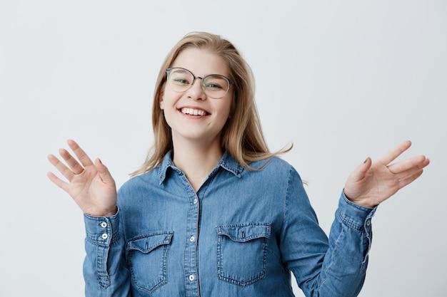 Sorridente femmina ampiamente positiva con capelli lisci biondi, indossa camicia di jeans, in posa contro il muro bianco grigio. ragazza felice dello studente che mostra le emozioni positive dopo aver ricevuto il buon segno